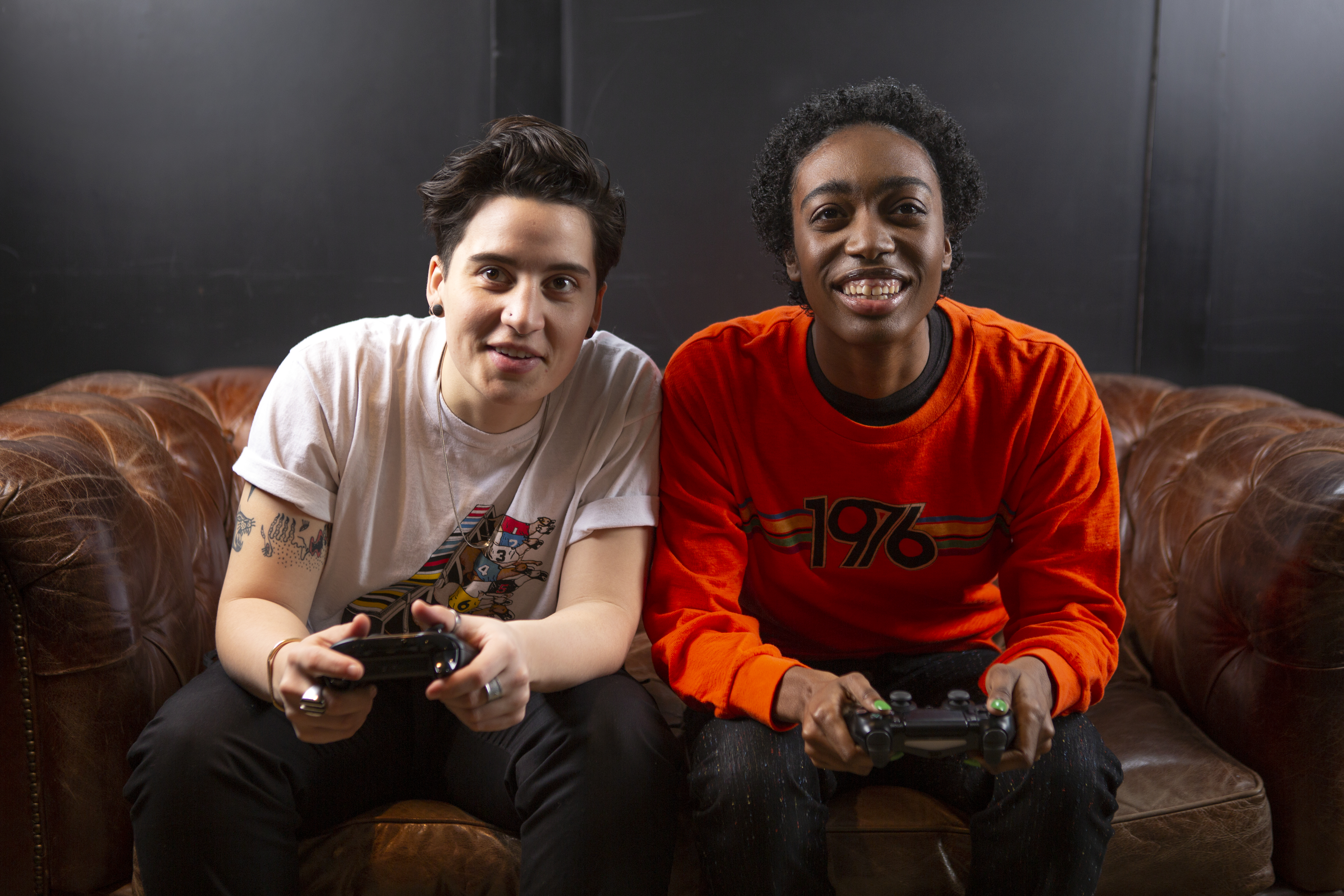 Two non-binary friends playing video games laughing